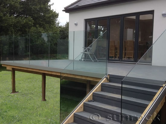 Infinity Glass Balustrades on a raised patio with wooden decking and steps